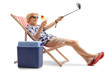 Happy Elderly Tourist With A Cocktail Taking A Selfie Isolated