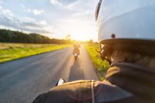Motorbike Riders Driving Towards Beautiful Sunset Light On Empty Asphalt Motorway.