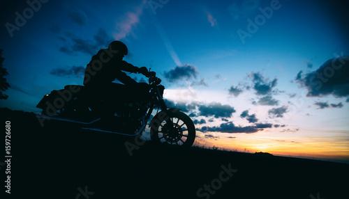 Dark motorbiker silhouette riding high power motorbike