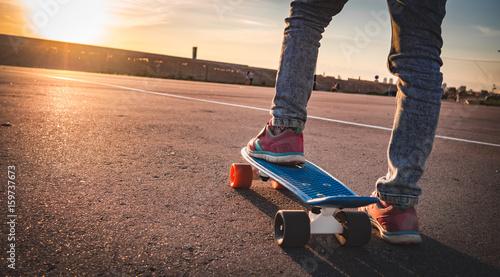 Zdjęcie XXL zbliżenie stóp na deskorolce na chodniku