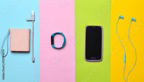 Power bank, smart watches, headphones, smartphone lined on a colorful background. Top View.