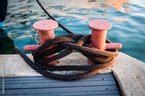 Fotografía  Mooring Bollard with rope on pier by the sea.