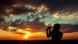 Silhouette of a man into sunset sky clouds