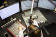 Female Jockey Using Music Mixers And Screens In Radio Studio