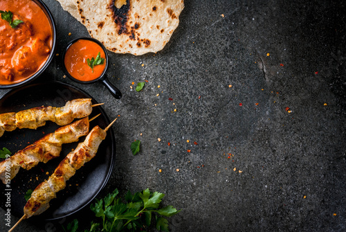 Indian food. Traditional dish spicy chicken tikka masala, butter chicken curry, with indian naan butter bread, spices, herbs. Served in bowl. sauce, on skewers. Stone dark table. copy space top view