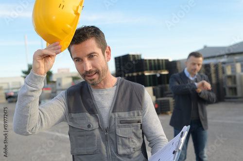 Photo  businessman looks his watch while factory worker leaves