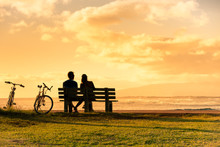 Couple Relaxing On A Park Bench Enjoying The Sunset.