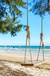 Wooden swing hanging from a tree on the beach , Chao Lao Beach, Chanthaburi in Thailand.