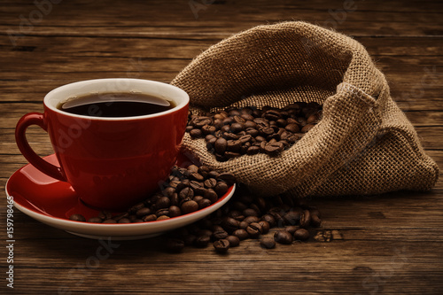 Cup of coffee and coffee beans with wooden table