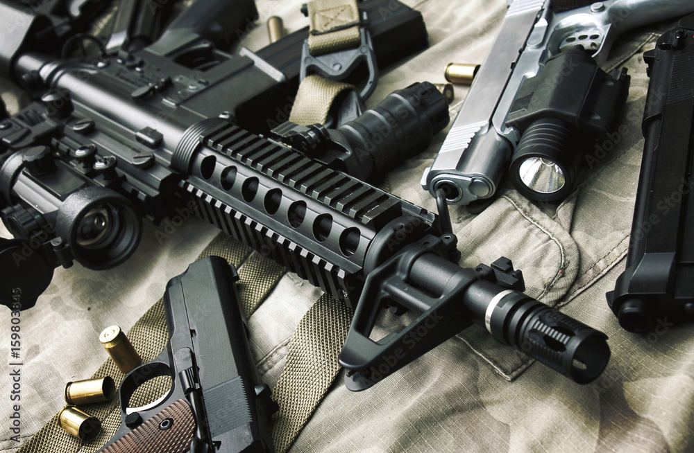 Fototapeta Weapons and military equipment for army, Assault rifle gun (M4A1) and pistol on camouflage background.