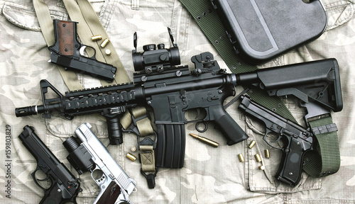 Fotomural  Weapons and military equipment for army, Assault rifle gun (M4A1) and pistol on camouflage background