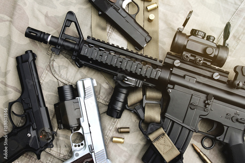 Weapons and military equipment for army, Assault rifle gun (M4A1) and pistol on camouflage background Canvas Print