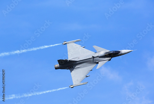 Foto Modern jet fighter flying against a blue sky. White smoke trail.