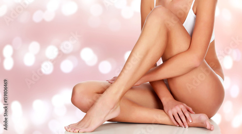 Obraz Young woman with beautiful body and smooth soft skin on an abstract background with blurred lights - fototapety do salonu