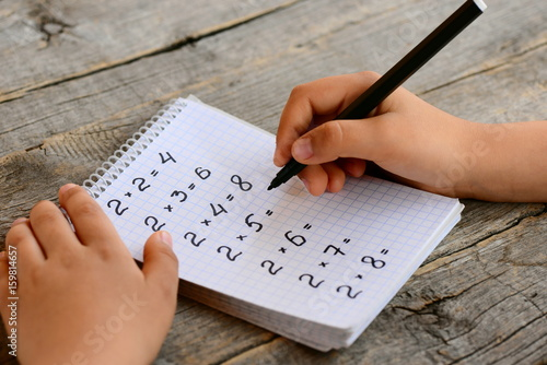 Student solves multiplication examples. Child holds a black marker in his hand and writes answers. Notebook with multiplication table examples. Teaching a multiplication table concept