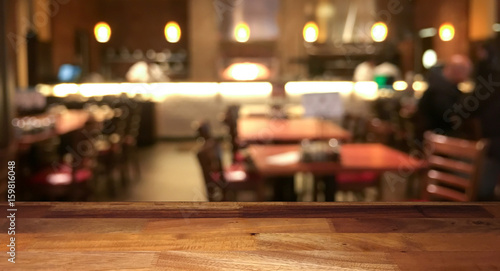 Foto op Canvas Restaurant Empty wooden table top with blurred restaurant on background