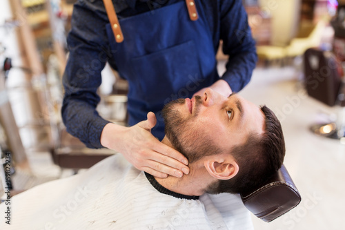 Photo barber applying aftershave lotion to male neck