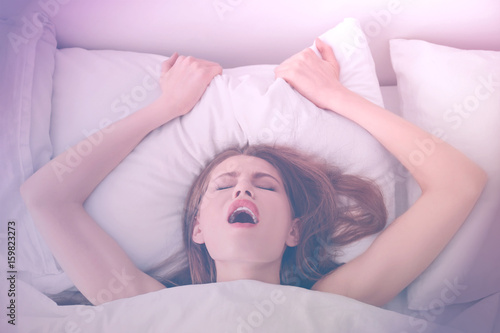 Beautiful woman getting sexual satisfaction in bed Canvas Print