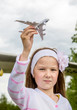 Little girl is playing with a toy airplane