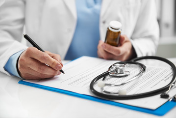 Female therapist writing prescription for patient holding medicine bottle. Concept of treatment and health care.