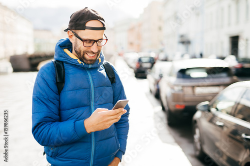 Photo Young bearded hipster guy in blue anorak and cap holding smartphone answering call having happy expression isolated over big city background
