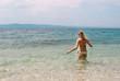 Young Caucasian female in bikini standing in shallow sea facing the horizon