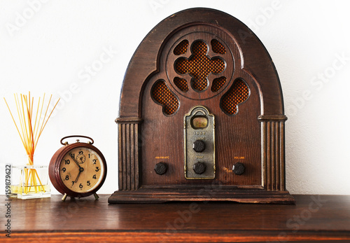 Fotografia  Close up view of antique wooden radio and broken clock with white wall in backgr