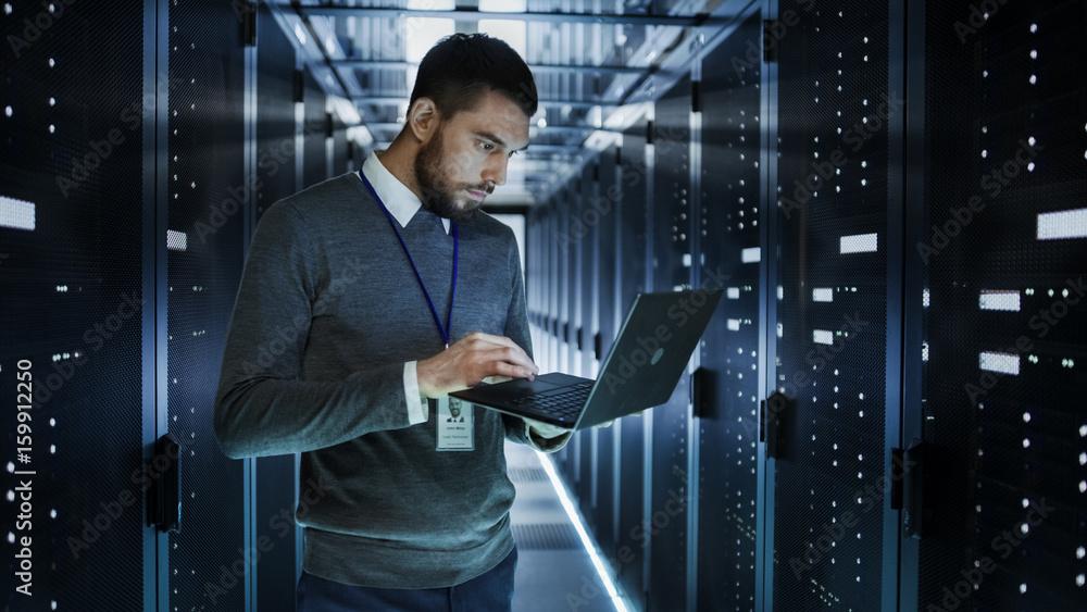 Fotografia IT Technician Works on a Laptop in Big Data Center full of Rack Servers