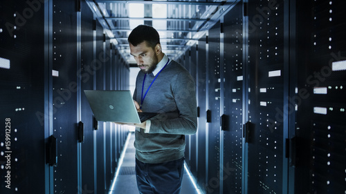 Stampa su Tela IT Technician Works on a Laptop in Big Data Center full of Rack Servers