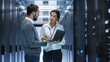 canvas print picture - Male IT Specialist Holds Laptop and Discusses Work with Female Server Technician. They're Standing in Data Center, Rack Server Cabinet is Open.