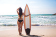Back view of surfer brunette girl with board relaxing on the beach of Dubai