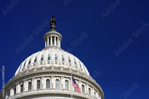 Fotografia, Obraz  US Capitol Building Dome with Clear Blue Sky & Flag