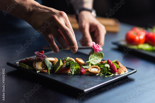 Photo Chef sprinkling spices on dish in commercial kitchen