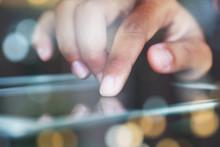 Close-up Finger Touching On Communicator Electronic Device On Night