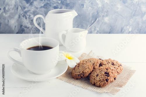 filizanka-kawy-z-mlekiem-i-malymi-ciasteczkami-na-bialym-talerzyku
