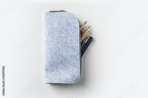 Cuadros en Lienzo Top view of grey fabric pencil case with lot of pens on white background desk fo