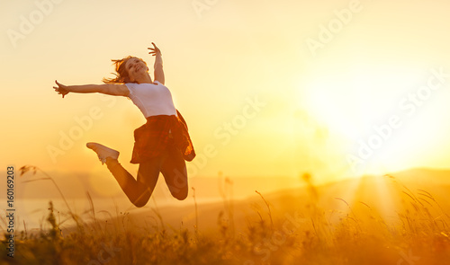 Happy woman jump, rejoices, on sunset in nature