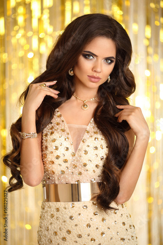 Fashion Jewelry Wavy Hairstyle Y Glamour Model Lady In Golden Dress With Gold Accessories Over Bokeh Lights Party Background Matte Lips See More