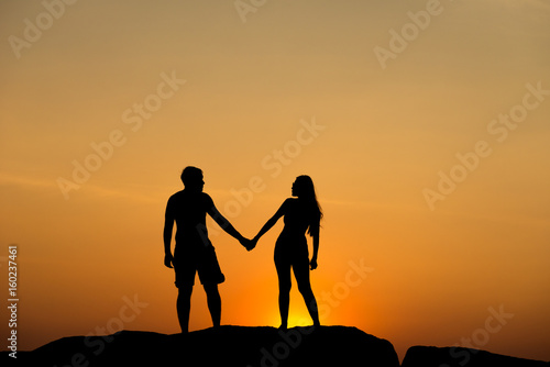Fototapety, obrazy: Silhouette of attractive confident half naked man and woman holding hands