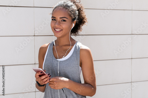 Fotografie, Tablou  Beautiful sporty woman listening to music, looking at camera