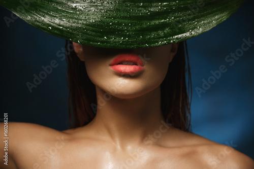 Fotografía  Closeup of shirtless woman with beautiful collarbone hiding behind leaf