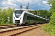 A modern electric regional train runs on a multi-lane track through natural surroundings
