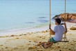 Man sitting on the swing on the tropical beach
