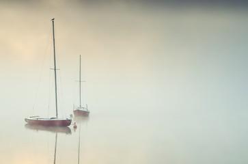 Obraz na Szkle Minimalistyczny Minimalist foggy morning landscape. Boats on the lake.