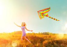 Beauty Girl In Short Dress Running With Flying Colorful Kite Over Clear Blue Sky. Freedom Concept.
