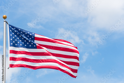 large american flag waving on flag pole with cloud blue sky windy