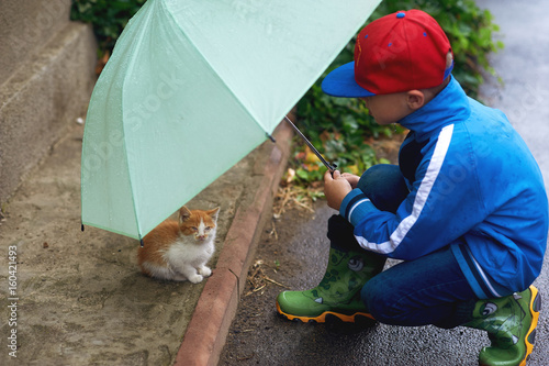 the child taking care of a kitten on the street , an umbrella sheltering him from the rain Fototapeta