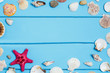 Wooden turquoise background with frame made of sea shells, top view