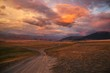 canvas print picture - Road path on a desert wild mountain plateau at the background of the hills under a dramatic sunset colorful sky with illuminated red pink purple clouds Kurai Altai Siberia Russia