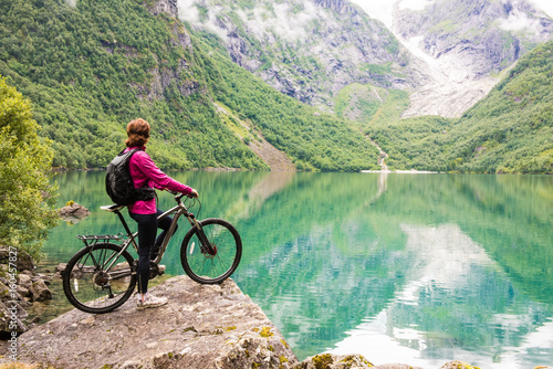 Deurstickers Olijf Biking in Norway against picturesque landscape